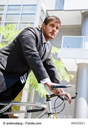 Junger Geschäftsmann auf einem Fahrrad