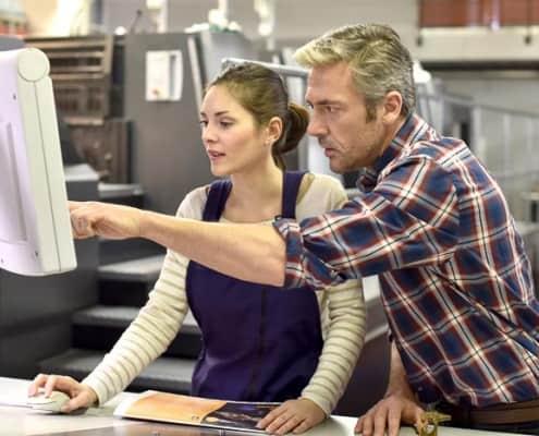 Firmeninhaber leitet junge Mitarbeiterin an